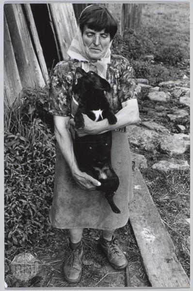 Habajka (Anna Habaj) - przed drewnianą ścianą z psem na rękach, 1985-1989, fot. Stanisław Ciok, MHF